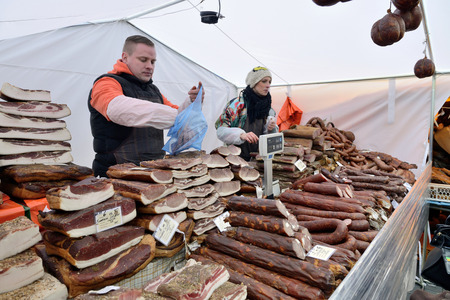 tradespeople: VILNIUS, LITHUANIA - MARCH 6: Unidentified people trade smoked meat in annual traditional crafts fair - Kaziuko fair on Mar 6, 2015 in Vilnius, Lithuania