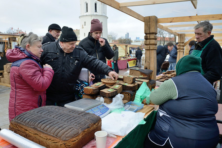 tradespeople: VILNIUS, LITHUANIA - MARCH 6: Unidentified people trade home made bread in annual traditional crafts fair - Kaziuko fair on Mar 6, 2015 in Vilnius, Lithuania
