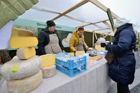 tradespeople: VILNIUS, LITHUANIA - MARCH 7: Unidentified people trade home made cheese in annual traditional crafts fair - Kaziuko fair on Mar 7, 2015 in Vilnius, Lithuania