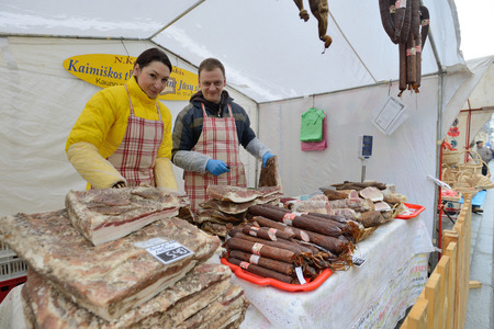 tradespeople: VILNIUS, LITHUANIA - MARCH 7: Unidentified people trade smoked meat in annual traditional crafts fair - Kaziuko fair on Mar 7, 2015 in Vilnius, Lithuania