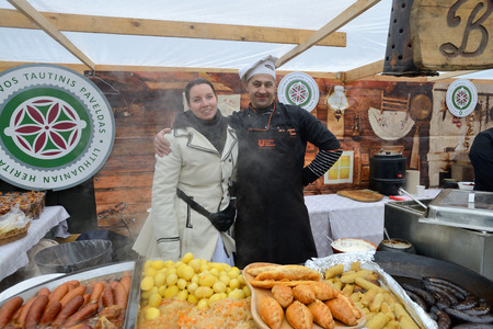 tradespeople: VILNIUS, LITHUANIA - MARCH 7: Unidentified people trade food in annual traditional crafts fair - Kaziuko fair on Mar 7, 2015 in Vilnius, Lithuania