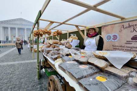 tradespeople: VILNIUS, LITHUANIA - MARCH 7: Unidentified people trade home made bread in annual traditional crafts fair - Kaziuko fair on Mar 7, 2015 in Vilnius, Lithuania Editorial
