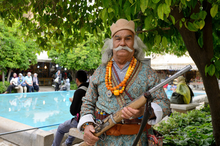 shiraz: SHIRAZ  APRIL 15: Unknown man with rifle posing in market Vakil Bazaar in Shiraz Iran on April 15 2015. Vakil Bazaar is the most important tourist attraction in Shiraz Iran. Editorial