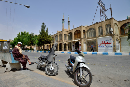 sunni: YAZD  APRIL 17: Unknown peoples and motorbikes in street of Yazd southern Iran on April 17 2015. Motorbike is main type of transport in a streets of Yazd capital of Yazd Province Iran. Editorial