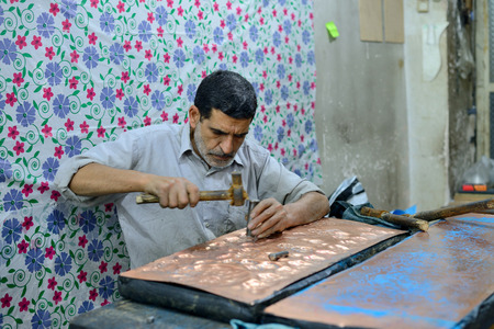 isfahan: ISFAHAN  APRIL 19: Unknown man making traditional iranian souvenirs in a market Isfahan Bazaar in Isfahan Iran on April 19 2015. Bazaar is the most important tourist attraction in Isfahan Iran. Editorial