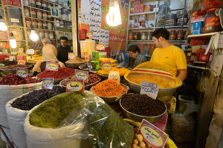 isfahan: ISFAHAN - APRIL 19: Unknown man trades traditional iranian food and spices in market (Bazaar) in Isfahan, Iran on April 19, 2015. Bazaar is the most important tourist attraction in Isfahan, Iran.