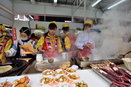 culinary tourism: SHANGHAI, CHINA - MARCH 19: Unidentified Chinese people trades traditional food on March 19, 2016 in Shanghai, China. Shanghai is the largest Chinese city by population.