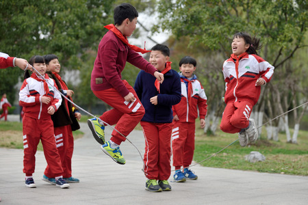 quintet: SUZHOU, CHINA - MARCH 22: Chinese school children play in park on March 22, 2016 in Suzhou, China. Suzhou is a major economic center and focal point of trade and commerce in Jiangsu Province, China.