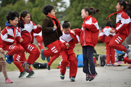 quintet: SUZHOU, CHINA - MARCH 22: Chinese school children play in park on March 22 2016 in Suzhou China. Suzhou is a major economic center and focal point of trade and commerce in Jiangsu Province China.