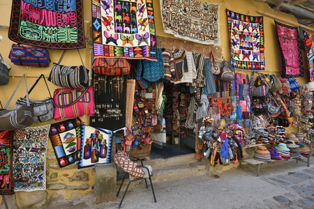 national historic site: OLLANTAYTAMBO, PERU - September 04, 2016: Colourful goods for sale in souvenir shop in Ollantaytambo, Peru on September 04, 2016. Ollantaytambo is a town and an Inca archaeological site in Peru.