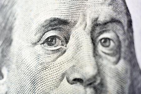 obverse: Benjamin Franklin face on USA one hundred dollar bill, macro close up