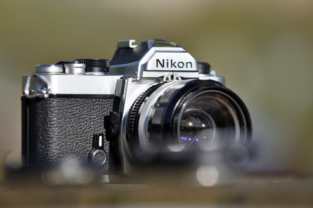 pixelated: VILNIUS - MAY 8: Nikon vintage film camera with Nikkor 35mm lens on May 8, 2017 in Vilnius, Lithuania. Nikon Corporation specializing in optics and imaging products.
