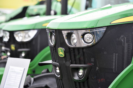 Kaunas, Lithuania - March 23: John Deere tractors and logo on March 23, 2018 in Kaunas, Lithuania. John Deere is the American corporation that manufactures agricultural and forestry machinery.