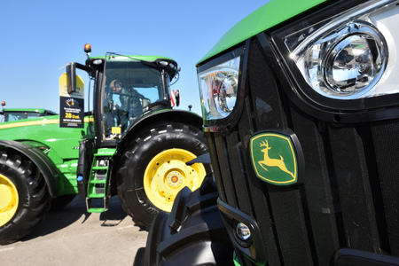 Kaunas, Lithuania - April 04: John Deere tractors and logo in Kaunas on April 04, 2019. John Deere is the American corporation that manufactures agricultural and forestry machinery.