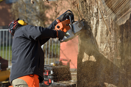Kaunas, Lithuania - April 04: Unidentified man cutting wood with Stihl chainsaw in Kaunas on April 04, 2019. Stihl is a German manufacturer of chainsaws and other handheld power equipment