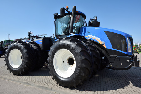 Kaunas, Lithuania - April 04: New Holland tractor and logo in Kaunas on April 04, 2019. New Holland is a global brand of agricultural machinery produced by CNH Industrial.