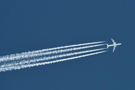 Aereo nel cielo blu con tracce di aereo