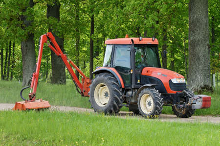 Bauska, June 01: Kioti tractor mow grass in large park on June 01, 2020 at Bauska, Latvia. Kioti Tractors the trade name for Daedong tractors in North America and Europe