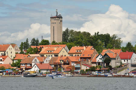 Mikolajki, Poland, July 12: View to city from the lake on July 12, 2020 at Mikolajki, Poland. Mikolajki is a resort town in the Warmian-Masurian Voivodeship in north-eastern Poland. Publikacyjne