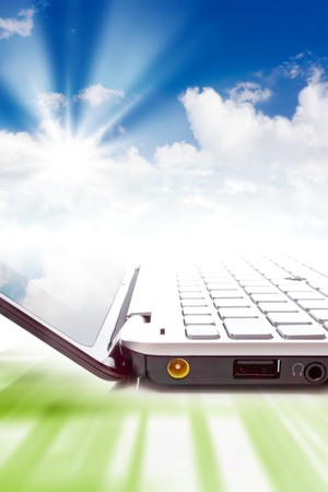 Concept - cloud computing, notebook and clouds in sky photo