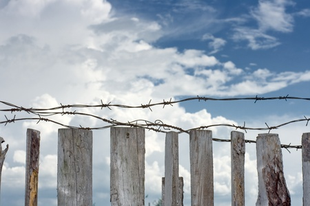 Barbed wire are stretched across top of wooden fence photo