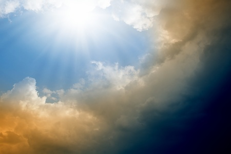 Dramatic impressive background -  blue sky with bright sun, dark clouds