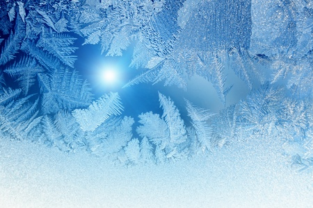 Abstract winter background - blue frozen window glass looks like fir-trees, bright sun.