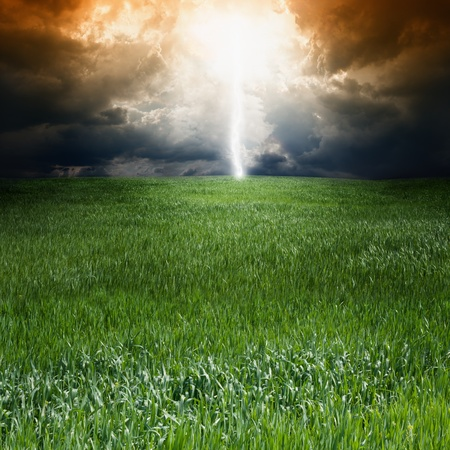 apocalyptic: Dramatic landscape with green field, dark sky and light from above