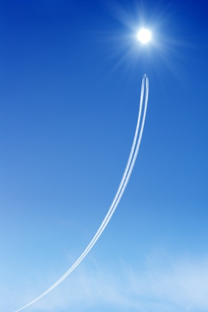 Jet aircraft rises to the bright sun in blue sky. Way to success. Concept of progress, improvement. photo