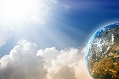 Peaceful background - planet  in blue sky, bright sun, white clouds photo