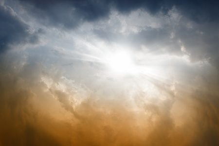 Dark sky, bright sun shines through clouds photo