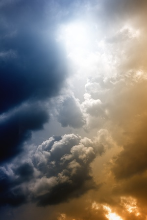 Abstract dramatic background - bright sun, dark clouds photo