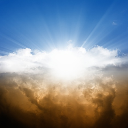 Dramatic background - bright sun in blue sky, white and dark clouds photo