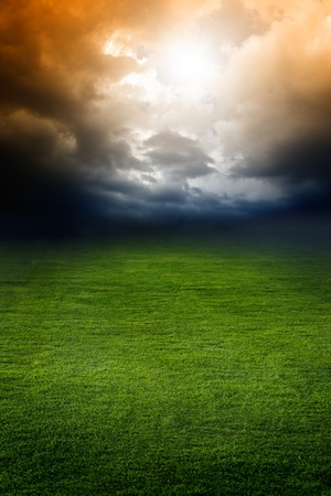Dramatic background - dark stormy sky, green field, bright light from above photo