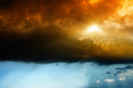 Dark dramatic sky with bright red sun photo