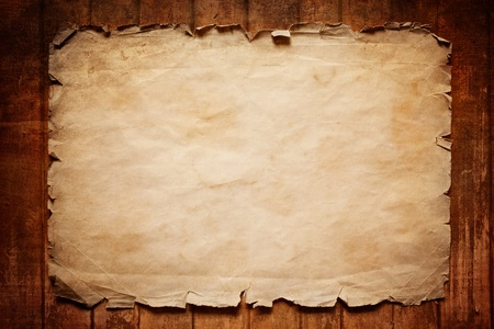 Abstract grunge background - old broken horizontal sheet of paper on brown wooden board