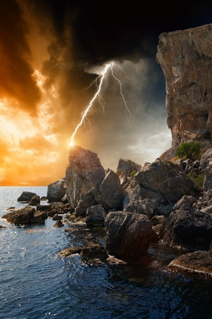 Dramatic nature background - rocks, sea, dark sky with lightning Stock Photo - 16749622