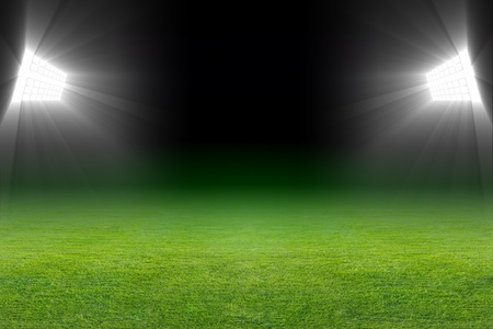 grass field: Green soccer field, bright spotlights, illuminated stadium