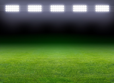 football field: Green soccer field, row of bright spotlights, illuminated stadium in night