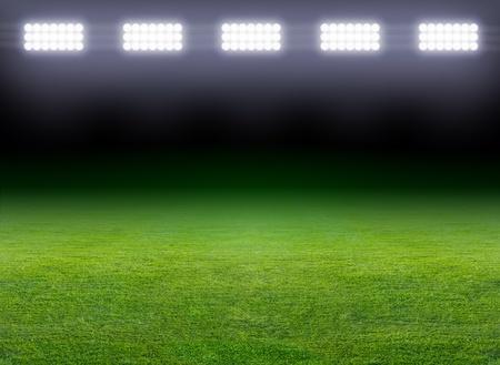 stadium: Green soccer field, row of bright spotlights, illuminated stadium in night