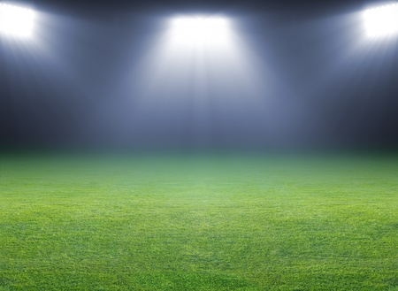 football stadium: Green soccer field, bright spotlights, illuminated stadium