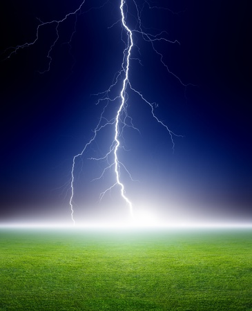 Big bright lightning, grenn grass field, dark blue night sky photo