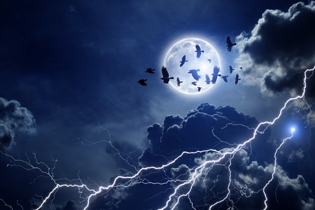 Night sky with full moon, lightning, dark clouds  Flock of flying ravens, crows in dark sky  Elements of this image furnished by NASA photo