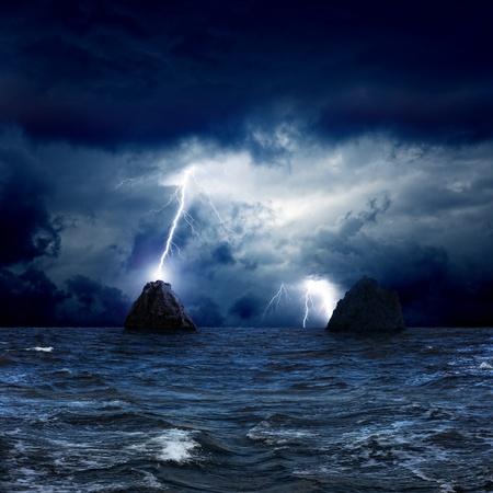lightnings: Dramatic nature background - lightnings in dark sky, two rocks in stormy sea