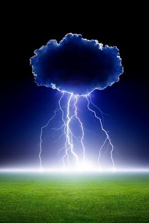 Big bright lightning from cloud, green grass field, dark night sky photo
