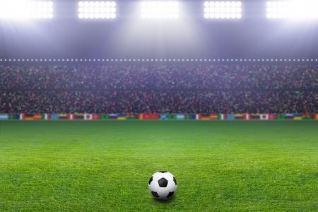 terrain foot: Ballon de football sur le stade vert, arène dans la nuit illuminée spots lumineux