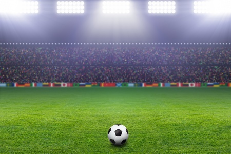 matches: Soccer ball on green stadium, arena in night illuminated bright spotlights