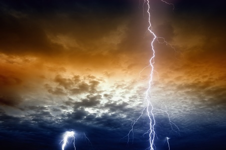Dramatic background - lightnings in sunset sky with dark red and blue clouds photo