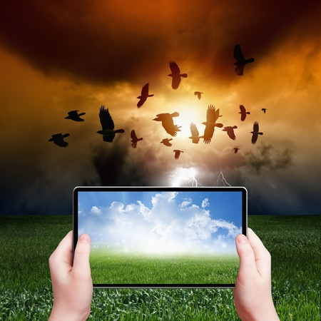 reality: Concept of augmented reality - abstract tablet pc in hands, sunny weather, stormy weather, flock of flying ravens, crows in dark sky with lightning