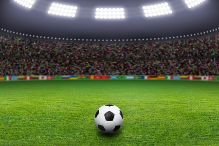 Soccer ball on green stadium, arena in night illuminated bright spotlights photo